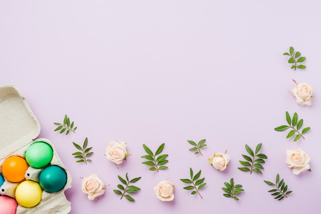 Collection lumineuse d'oeufs colorés dans un récipient près des fleurs et des plantes