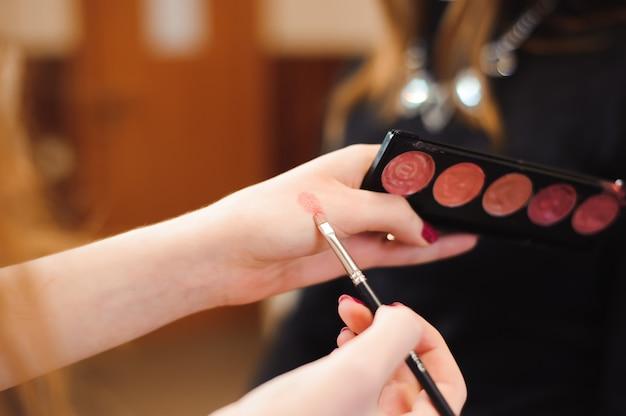 Collection de maquillage de rouge à lèvres dans les mains du maître