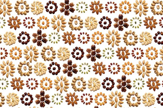 Une collection de noix à base d'amandes, de noix, de noisettes, de pistaches, de noix de cajou se trouve en forme de cercle ou de soleil sur un mur blanc isolé. motif de noix divers