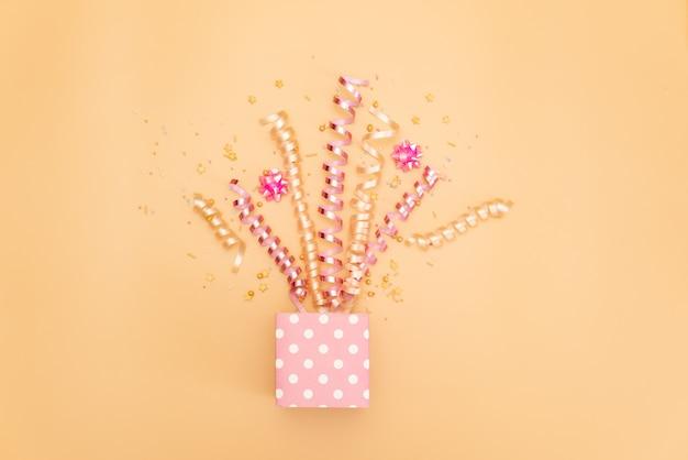 Collection d'objets de fête d'anniversaire rose dans une boîte cadeau
