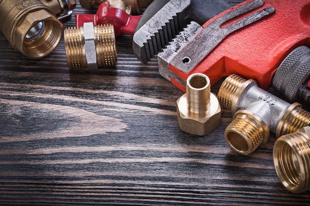 Collection d'outils de plomberie en laiton sur planche de bois