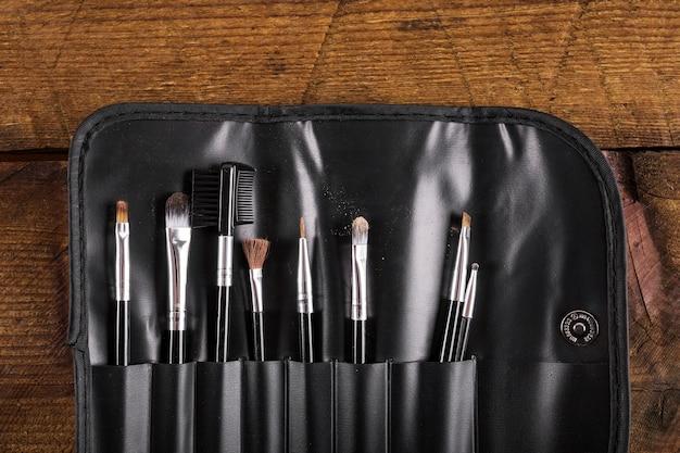 Collection de pinceaux de maquillage divers sur fond en bois