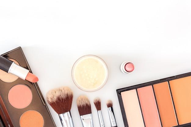 Une collection de pinceaux, de produits de maquillage et de produits de beauté cosmétiques disposés sur un fond blanc