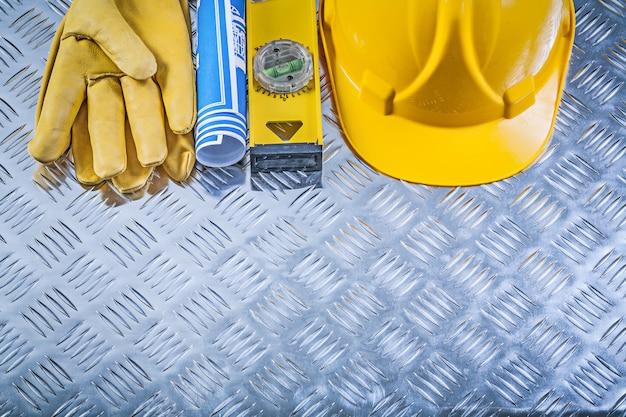 Collection de plans laminés bleus bâtiment gants de sécurité casque niveau de construction sur fond de tôle ondulée