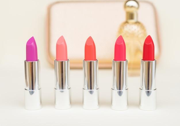 Collection de rouges à lèvres brillants puple, roses et rouges devant la femme d'or poursuivent
