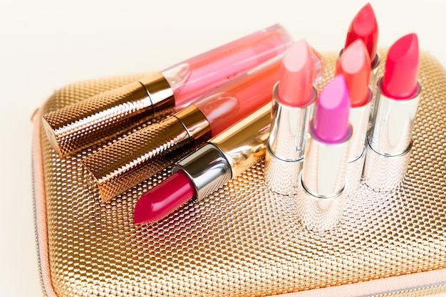 Collection de rouges à lèvres colorés sur le sac de poursuite d'une femme dorée