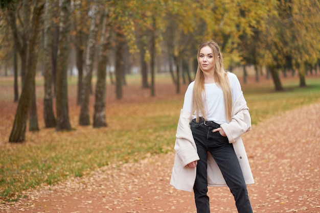 Collection de rue moderne. jeune fille blonde confiante vêtue d'une chemise blanche, d'un jean noir et d'un manteau d'automne tendance