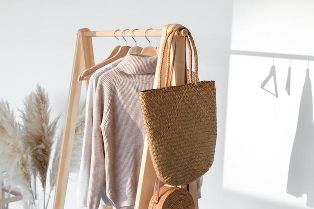 Une collection de vêtements, dans des tons beiges, accrochée à un cintre dans le dressing. matière naturelle.