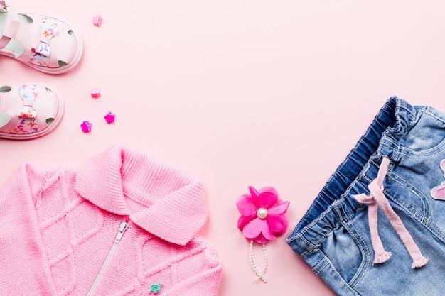 Collection de vêtements de petite fille à plat avec t-shirt à fleurs, jeans, sandales sur fond rose.