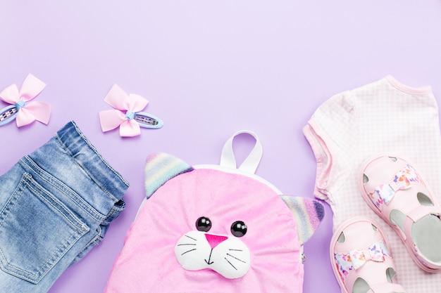 Collection de vêtements de petite fille à plat avec t-shirt, jeans, sandales, sac à dos sur fond pastel.
