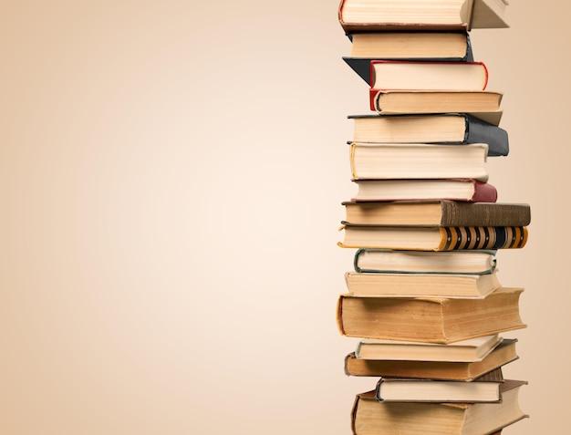 Collection de vieux livres pile verticale sur fond beige
