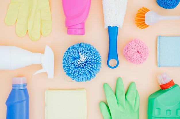 Collection vue de dessus de produits de nettoyage colorés sur fond de pêche