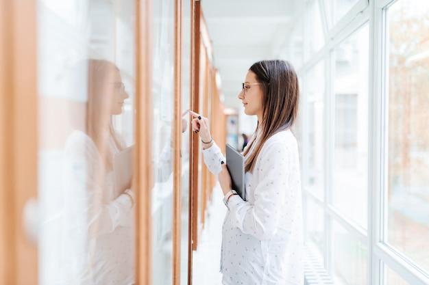 College girl holding tablet et à la recherche sur le tableau d'affichage