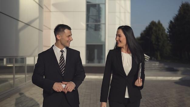 Collègue d'affaires - jeune homme exécutif et femme d'affaires attrayante à l'extérieur pendant la pause par une chaude journée d'été