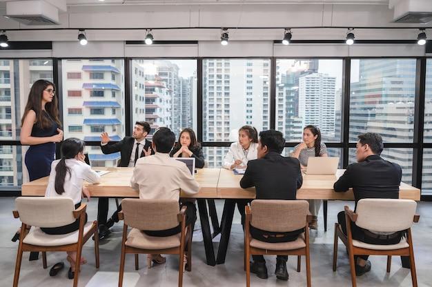 Collègue de l'équipe commerciale multiethnique réunion sérieusement et discuter sur table de conférence dans un bureau moderne