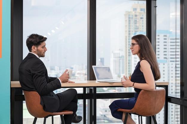 Collègue d'homme d'affaires caucasien discuter et boire pendant la pause en milieu de travail au coin bureau
