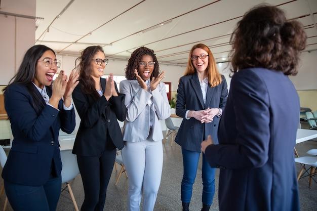 Collègue mature parlant à des collègues plus jeunes heureux