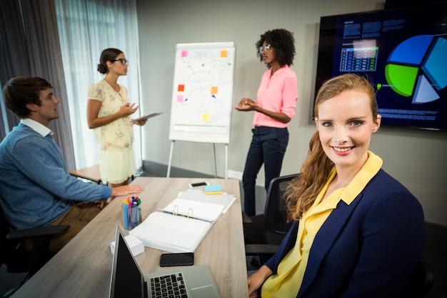 Un collègue souriant à la caméra pendant que des collègues discutent de l'organigramme sur le tableau blanc