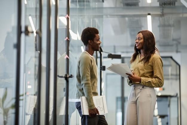 Des collègues d'affaires afro-américains positifs et amicaux qui parlent dans le couloir du bureau après m'avoir réussi...