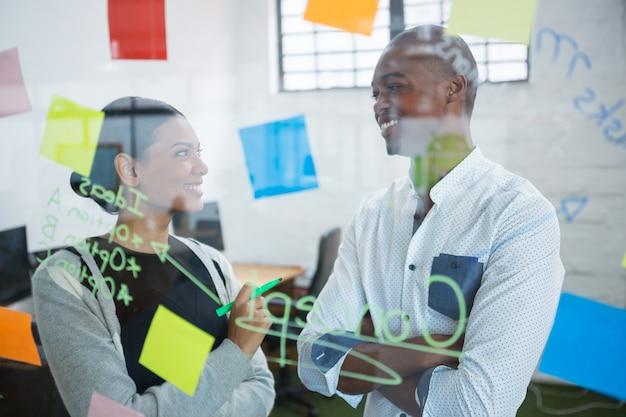 Collègues d'affaires interagissant les uns avec les autres tout en écrivant sur pense-bête
