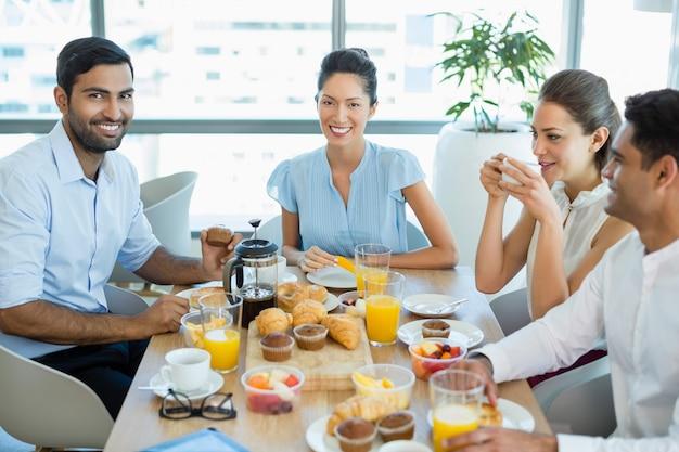 Collègues d'affaires interagissant entre eux tout en prenant le petit déjeuner