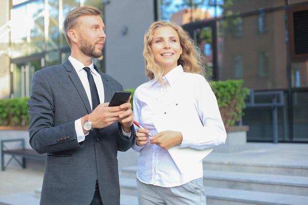 Collègues d'affaires regardant un téléphone portable debout près d'un immeuble de bureaux.