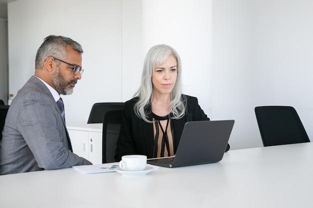 Collègues amicaux utilisant un ordinateur portable pour un appel vidéo, assis à table avec une tasse de café, regardant l'affichage et parlant. concept de communication en ligne