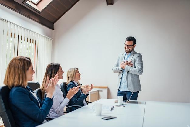 Collègues applaudissant le succès d'un jeune chef d'entreprise lors d'une réunion d'équipe.