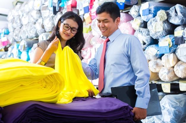 Collègues asiatiques dans un entrepôt en choisissant des tissus