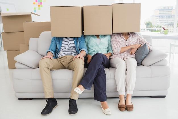 Collègues assis sur un canapé couvrant avec une boîte en carton