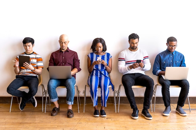 Collègues assis dans une rangée utilisant des appareils numériques
