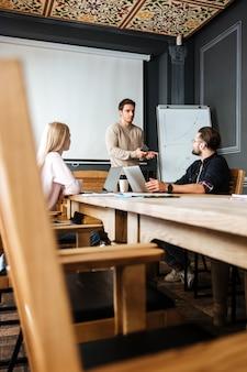 Des collègues attrayants travaillent avec des ordinateurs portables et des ordinateurs portables.