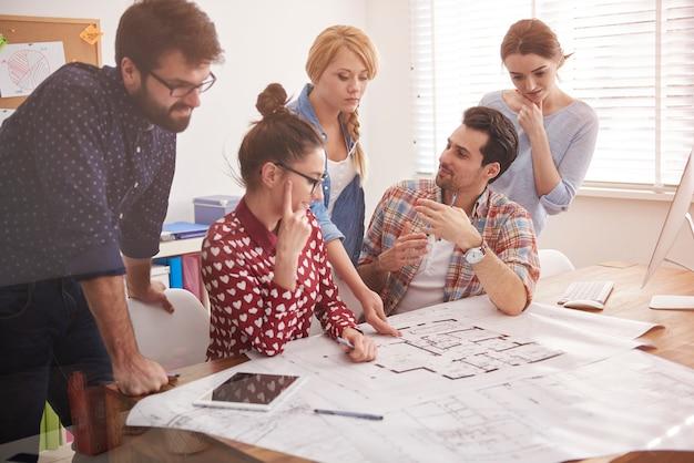 Collègues au bureau avec des plans d'architecture et un ordinateur
