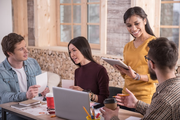 Collègues au travail. joyeuse belle femme positive tenant une tablette et regardant ses collègues tout en se tenant près d'eux