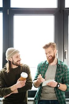 Collègues de beaux hommes au bureau parler les uns avec les autres