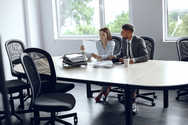 Collègues boivent du café. partenaires commerciaux lors d'une réunion d'affaires. homme et femme assis à la table