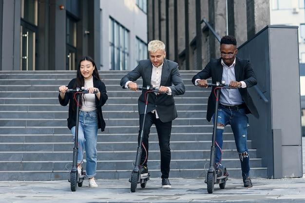 Collègues de bureau multiracial joyeux drôles ayant compétition de course sur des scooters électriques près de moderne