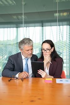 Collègues de bureau sérieux regardant le contenu sur tablette ensemble, regardant l'écran.