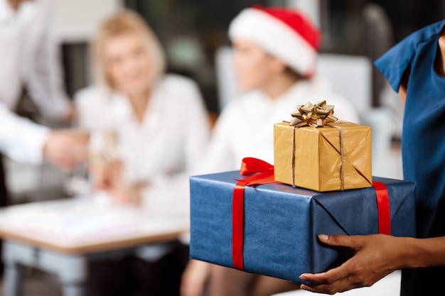 Collègues célébrant la fête de noël au bureau en souriant donnant des cadeaux.