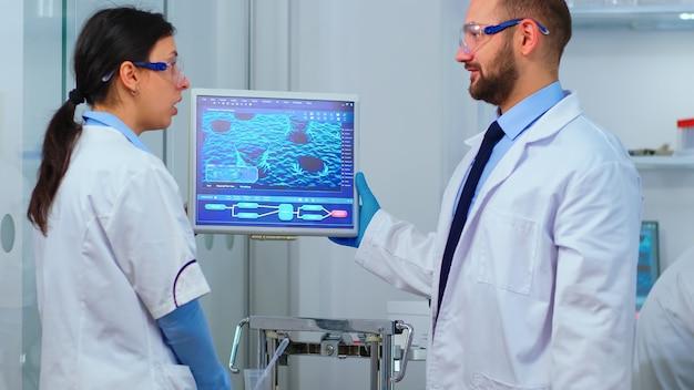 Des collègues chimistes prévoient d'effectuer un vaccin contre un nouveau virus dans un laboratoire équipé de façon moderne. des trucs multiethniques analysant l'évolution des vaccins à l'aide de la haute technologie pour rechercher un traitement contre covid19