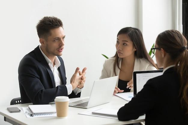 Des collègues concentrés discutant des stratégies commerciales de l'entreprise
