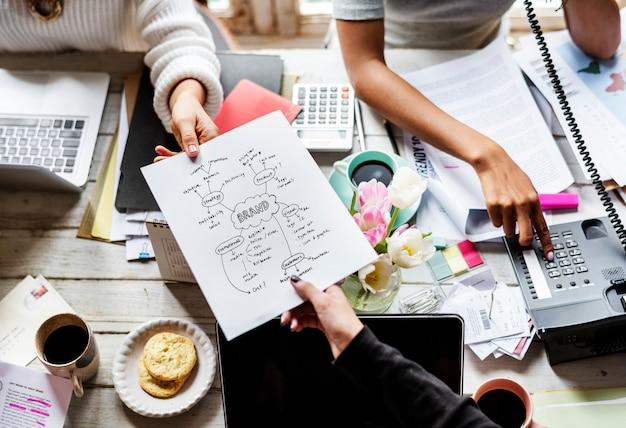 Collègues confiant la stratégie du plan de marque à d'autres