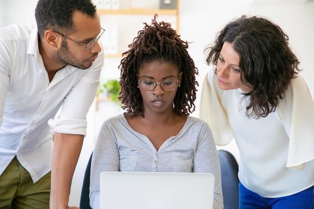 Collègues confiants parler tout en travaillant avec un ordinateur portable