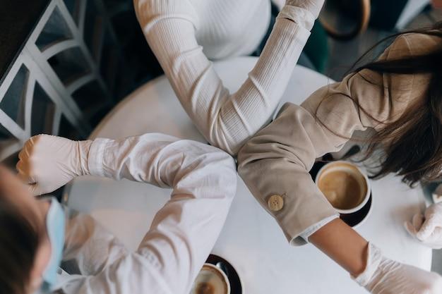Collègues dans les masques de protection donnant cinq haut avec les coudes dans le bureau. les femmes travaillent pendant le coronavirus