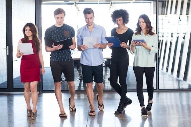 Collègues debout dans le bureau avec document et tablette numérique