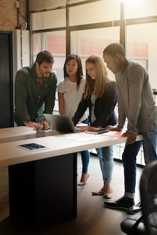 Collègues debout devant un bureau en passant par une présentation sur ordinateur