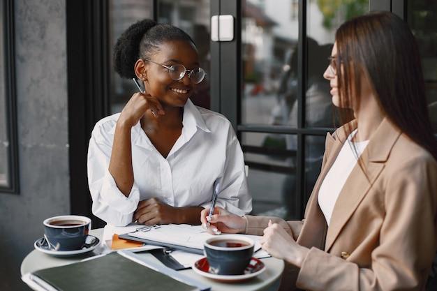 Collègues discutant des données dans le café en plein air. femmes multiraciales analysant une stratégie productive pour la projection d'affaires à l'aide de documents dans un café de la rue
