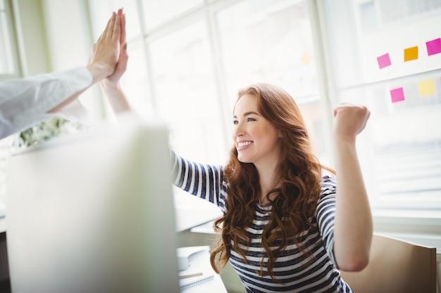 Des collègues enthousiastes donnant un high-five au bureau créatif