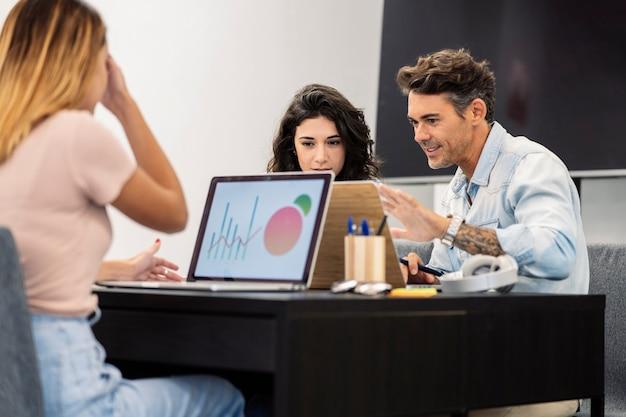 Des collègues féminines en coworking avec des ordinateurs, un homme mûr et une jeune fille de race blanche