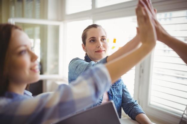 Collègues féminines donnant un high-five dans le bureau créatif